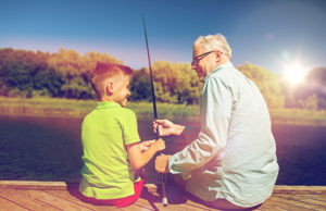 family, generation, summer holidays and people concept - happy grandfather and grandson with fishing rods on river berth
